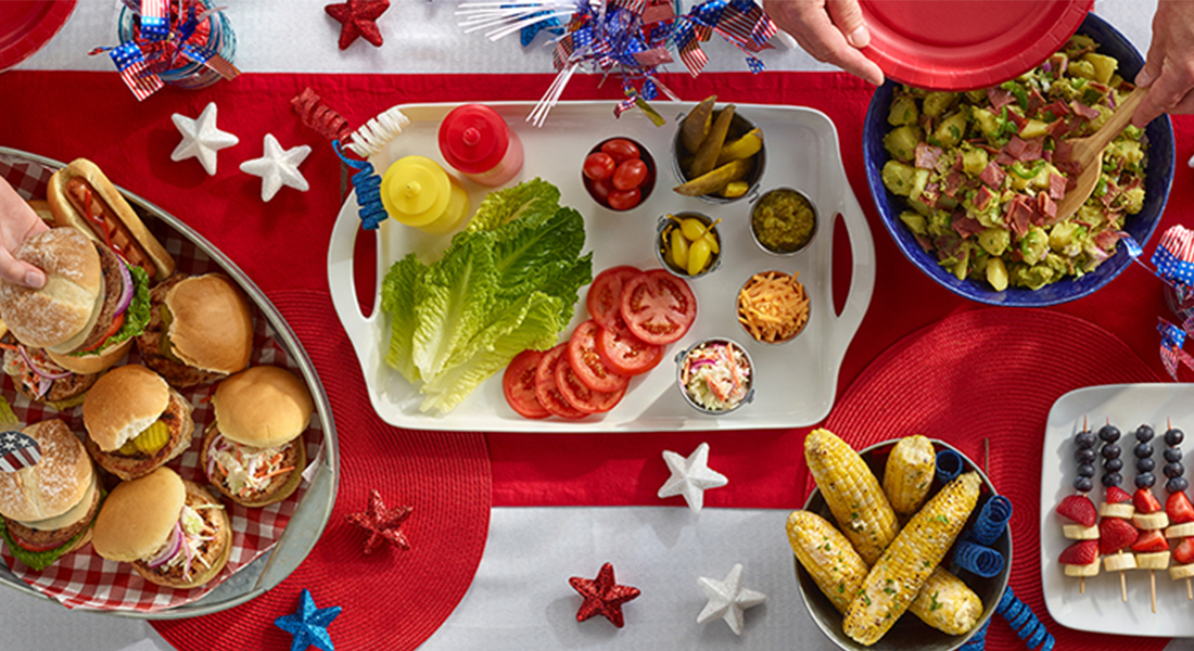 Numerous turkey burgers, each with different toppings, along with a hot dog sit upon a red and white checkered napkin, all of which is within a metal container. A white plastic tray of toppings sits at the center, separated Romain lettuce, sliced red tomatoes, cherry tomatoes, jalapeño peppers, cheddar cheese, cold slaw, pickles and pickled relish. A bowl of salad, another of corn on the cob, and a plate of fruit kabobs made of bananas, strawberries and blueberries complete the barbeque spread. All of the dishes sit on a star covered white and red table cloth.