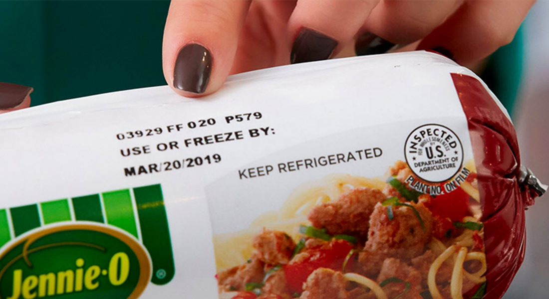 "An off screen figure points to the ""Use or Freeze By:"" date on a JENNIE-O® brand ground turkey container."