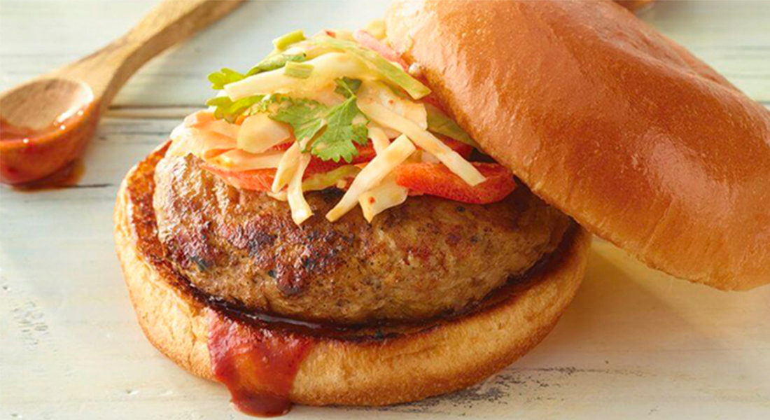 A turkey burger sits on a brioche bun with a barbeque sauce spread, topped with a mix of cabbage, peppers, cilantro, and kimchi while a wooden spoon with residual barbeque sauce sits in the background, both on a granite surface.