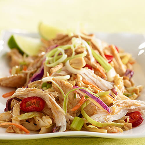 Vegetables, coleslaw mix, and turkey combine with crispy noodles to create an Asian-inspired salad, served ona white plate garnished with lime wedges, atop a green cloth.