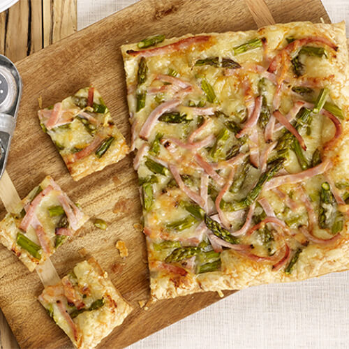 Savory turkey, crisp asparagus and melted cheese served on a golden brown puff pastry, served on a wooden pizza board.