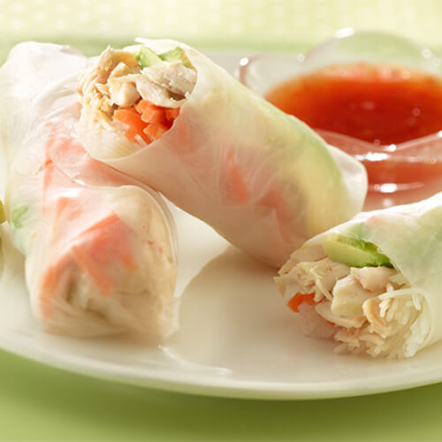 Shredded turkey, avocado and noodles rolled in rice paper and served with a sweet chili sauce, on a white plate garnished with a lime wedge, on a green cloth.