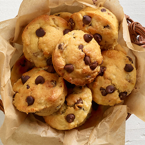 Rich, indulgent muffins made with chocolate and bananas, served on parchment paper in a wood woven bowl, atop a wooden table.
