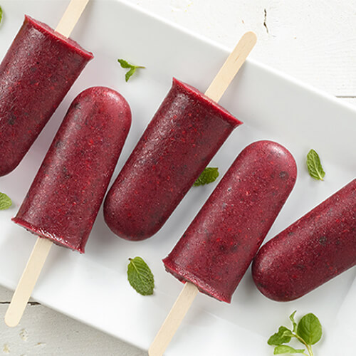 Delicious popsicles made with fresh blackberries, sugar, and mint leaves, served on a white plate atop a wooden table.