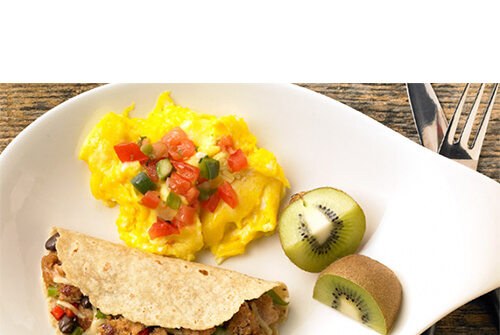 A great portion of eggs topped with peppers, served with a hearty portion of peppers, beans, and ground turkey in a tortilla, with a side of kiwi wedges, on a white plate atop a wooden table.