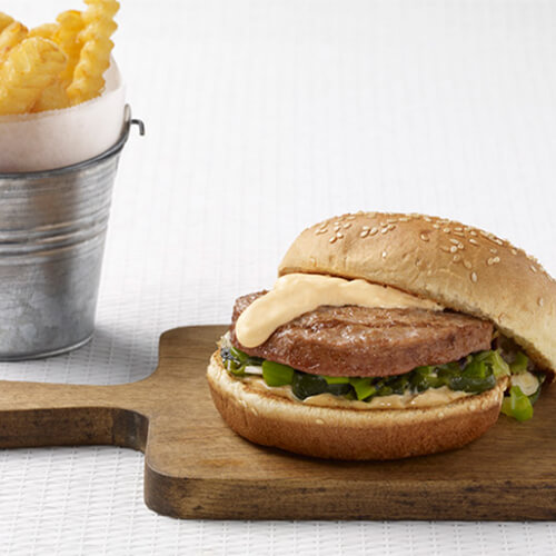 A grilled turkey burger topped with grilled onions and peppers, a spicy aioli and a melted cheese sauce, served on a wooden board and a small metal bucket filled with crinkle cut french fries.