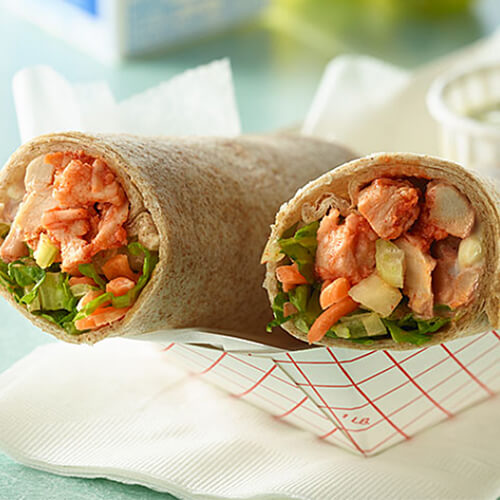 A wrap filled with turkey, Buffalo sauce, and veggies, served with a blue cheese dressing in a paper bowl.