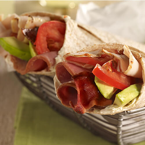 2 crispy flour wraps filled with turkey breast, turkey ham, creamy avocado, and fresh tomatoes in a woven bowl on a wooden table.