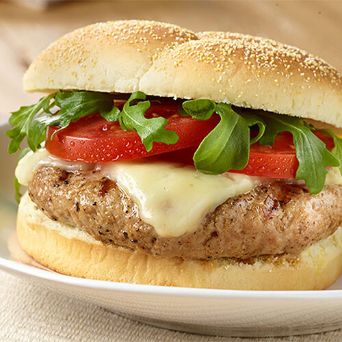 California turkey burger with melted cheese on a white plate.