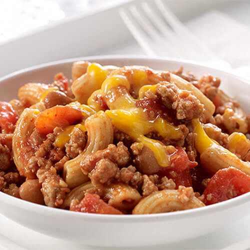 Macaroni combined with ground turkey, tomatoes, pinto beans and taco seasoning, served in a white bowl on a white plate.