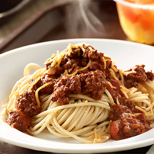 A hearty portion of spaghetti noodles, cheese and Cincinnati-style meat sauce, served in a white bowl.