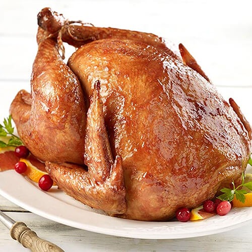 A whole turkey covered with a cranberry glaze, atop a variety of berries and fruits, atop a white plate.