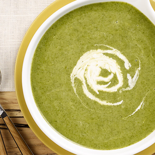 A creamy spinach soup served in a green bowl on a linen tablecloth.