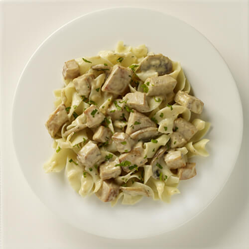 A creamy stroganoff made from mushrooms, roasted turkey breast, sauteed onion and garlic, served over noodles, garnished with parsley.