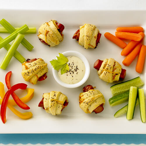 Crescent rolls wrapped around JENNIE-O® turkey franks served with vegetable with a honey mustard sauce, served on a white tray on a blue place mat with a white background.