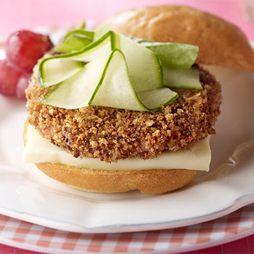 A crispy breaded turkey burger topped with soft brie cheese and crunchy cucumber garnished with tomatoes, served on white and checkered plates, and on a pink tablecloth.