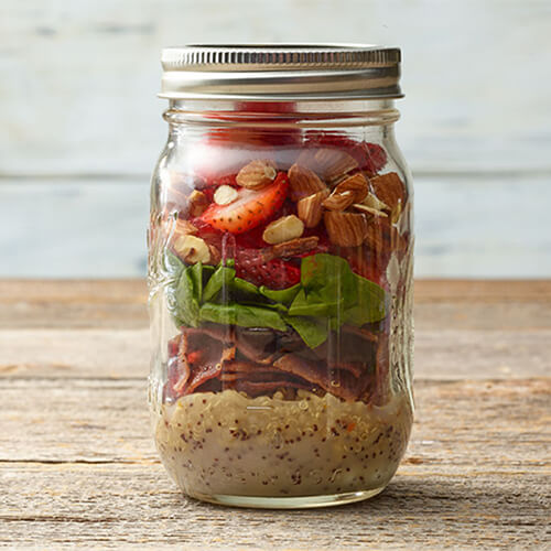 A lemon-poppyseed dressing, quinoa, turkey bacon, spinach, strawberries and almonds all served in a mason jar on a wooden table.