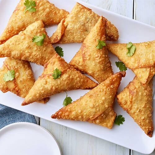 Turkey samosas garnished with cilantro stacked on a white plate.