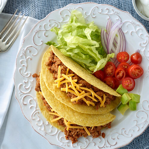 Turkey tacos made with cheese, lettuce, onion, and tomatoes, served on a white plate, on a blue woven tablecloth.