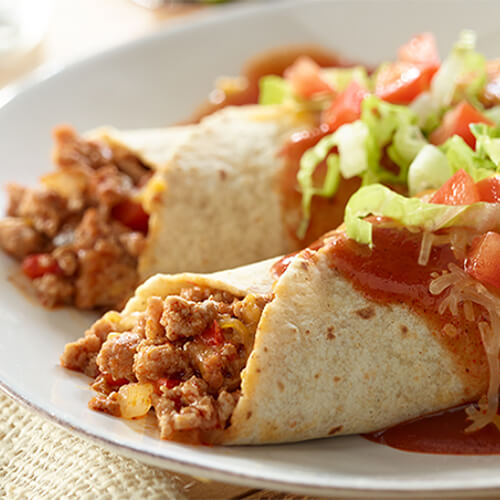 Two enchiladas in flour tortillas filled with ground turkey meat, onions, and topped with enchilada sauce, tomatoes, and shredded lettuce.