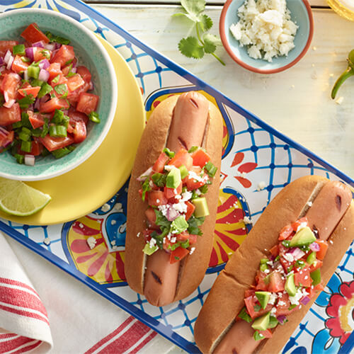 Fiesta turkey dog with salsa on a blue painted plate.