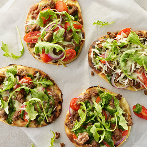 Flatbread turkey sausage pizza with the toppings overflowing on a white table.