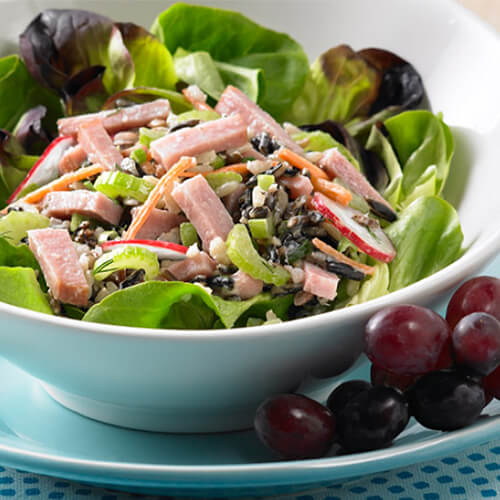 Strips of turkey ham joining spicy radishes, julienned carrots, celery and green onion, served on a blue bowl garnished with grapes, on a blue patterned cloth.