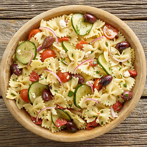 Cucumber slices, onion, olives, red bell pepper, tomatoes, herbs, and farfalle pasta served in a wood bowl garnished with feta, on a wooden table.