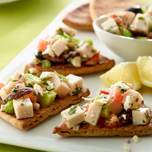 Wedges of pita bread, topped with turkey, olives, tomato, and parsley, served on a white platter with lemon wedges.