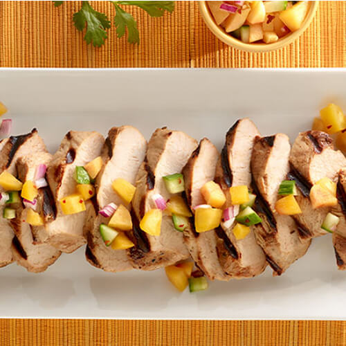 Juicy slices of turkey topped with fresh salsa, on a white platter, served on a colorful tablecloth.