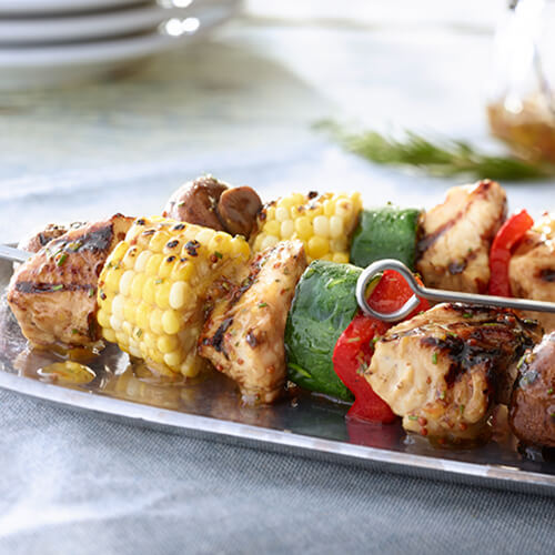 Kabobs made from mushrooms, zucchini, bell peppers, corn, and turkey tenderloins drizzled with a marmalade glaze on a metal plate on a gray tablecloth.