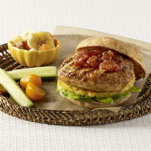 A turkey burger with grilled pineapple, lettuce, and topped with a combination of pineapple preserves and barbecue sauce, in a woven plate with a side of vegetables in a white background.