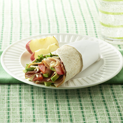 A wrap filled with fresh-sliced hickory-smoked turkey, bacon, and packed with vegetables, serves with a side of apples and sparkling water, on a white plate, atop green cloths.