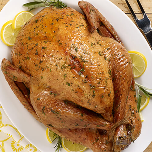A juicy honey glazed turkey garnished with lemon slices and herbs, served on a white plate atop a wooden table.