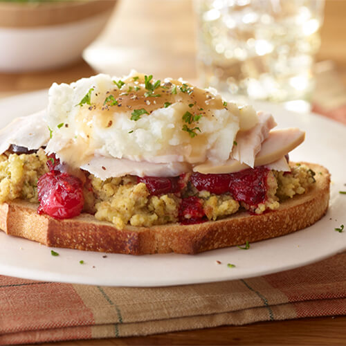 An open-face sourdough sandwich topped with stuffing, cranberry sauce, lean turkey, mashed potatoes and gravy, served on a white plate, garnished with parsley.