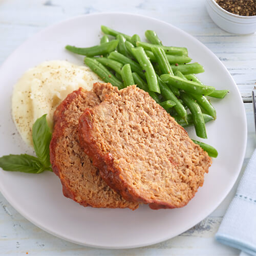 Two thick slices of meatloaf over a side of mashed potatoes and seasoned green beans on a white plate.
