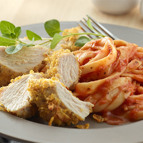 Turkey made with a savory parmesan cheese breading, served with a pasta made with marinara, on a grey shallow plate.