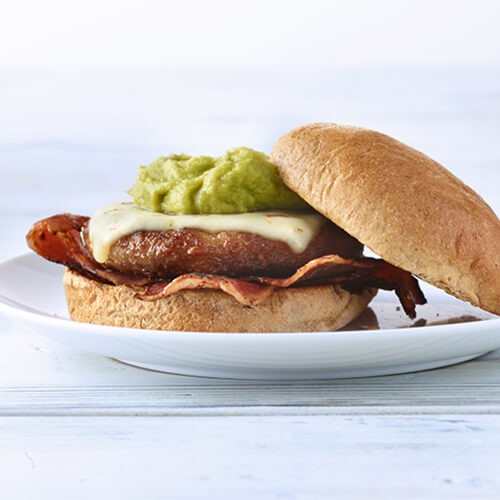 An amazing turkey burger topped with bacon strips, guacamole and melted pepper jack cheese. served on a white plate on a wooden table.