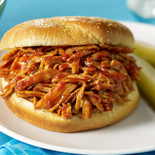 A hearty portion of barbecue sauce covered turkey, served on a white plate with a side of pickles and coleslaw, on a cyan tablecloth.