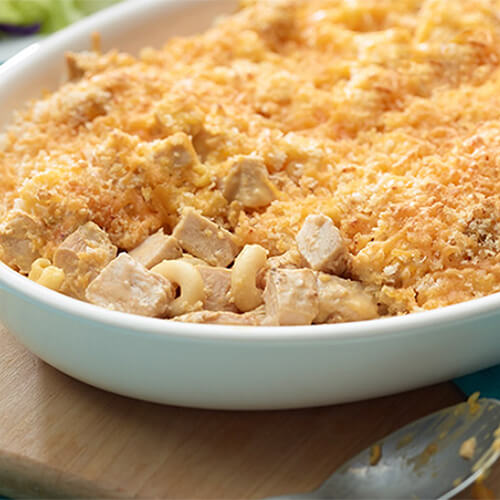 A creamy breaded pasta bake filled with macaroni, cheese, and turkey, served in a white tray on a wooden block.