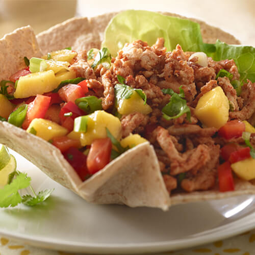 A hearty taco salad filled fresh mango salsa, veggies, and seasoned ground turkey, topped with cilantro, garnished with cilantro and lime wedges served on a white plate.
