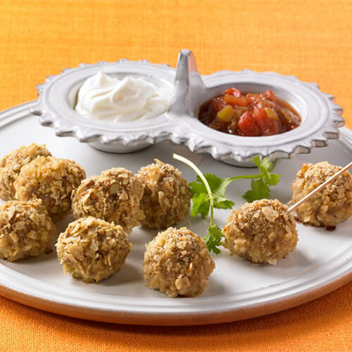 Bite-sized, coated, turkey meatballs, garnished with cilantro, served with a side of sour cream and salsa, served on a white plate.