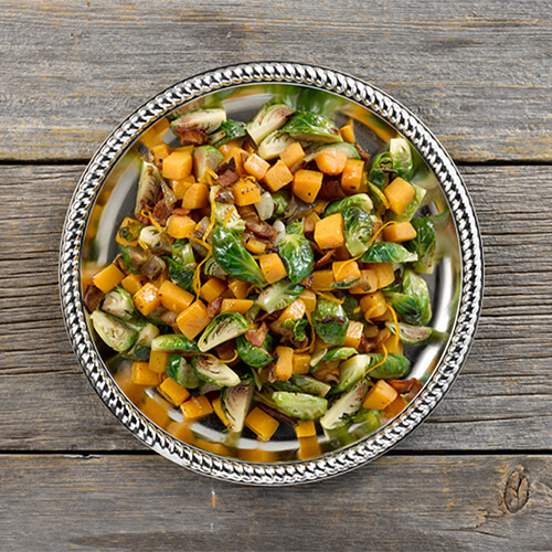 Orange glazed brussels sprouts and butternut squash in a grey bowl on a wood table.