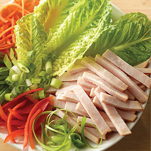 A white plate leafy Romaine lettuce, carrot strips, strips of JENNIE-O® Turkey Breast and red bell pepper slices.