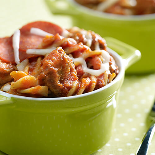 Rotini filled with pasta sauce, pepperoni, cheese, and ground turkey, all in a green pasta bowl.