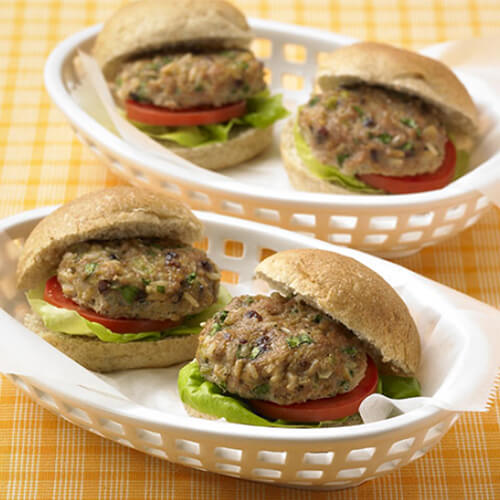 Sliders made with turkey, cranberries, and brown rice, with lettuce, tomatoes and onions served in a white serving basket on a yellow tablecloth.