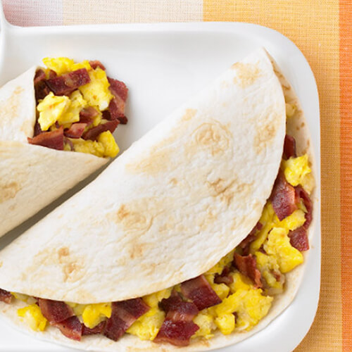 2 hearty breakfast burritos, stuffed with scrambled eggs, turkey bacon and colby cheese in a warm flour tortilla, garnished with orange slices and a sprig of cilantro, and served with salsa, in a white tray, on a vibrant tablecloth.