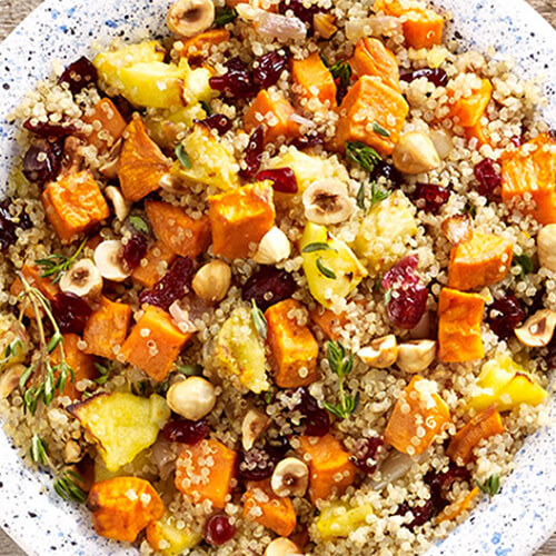 Potatoes and quinoa mixed with fall flavors such as sweet potatoes, apples & hazelnuts, served in a white plate atop a wooden table.
