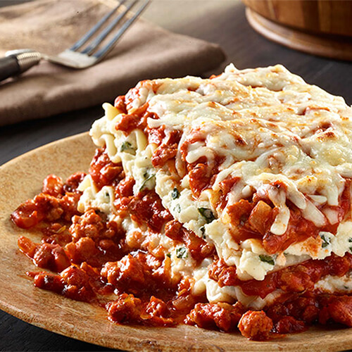 A hearty classic lasagna filled with ground turkey, basil, pasta sauce, ricotta, asiago, and mozzarella cheeses, on a wooden plate and table.