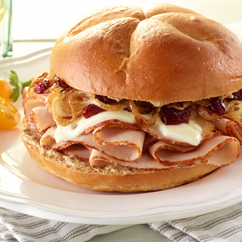 A grainy bun, with the combination of tastes of sweet caramelized onions, a tart cranberry sauce, the nutty taste of melted Swiss cheese, combined with the savory tastes of turkey and mustard, served on a white plate garnished with roma tomatoes.